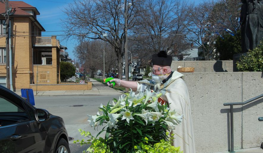 In this Saturday, April 11, 2020, file photo, the Rev. Timothy Pelc blesses Easter baskets outside St. Ambrose Church in Grosse Pointe Park, Mich. Pelc, wearing church vestments and protective gear, offered a prayer and sprayed holy water from a squirt gun instead of blessing baskets inside the church in a bid to maintain social distancing during the coronavirus pandemic. (Natalie White via AP) ** FILE **