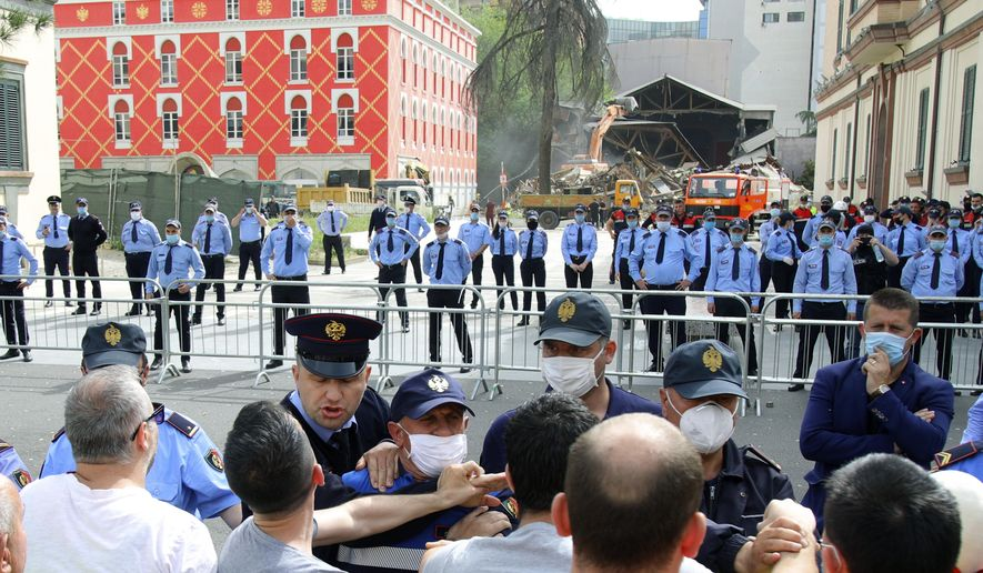 Protesters scuffle with police during the demolition of the national theater building in Tirana, Sunday, May 17, 2020. The government's decision to destroy the old National Theater, built by Italians when they occupied Albania during World War II, was opposed by artists and others who wanted it renovated instead. (AP Photo/Gent Onuzi)