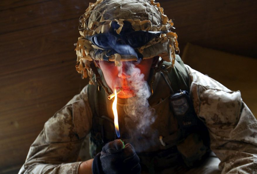 Lcpl. Charles Williams from Lafayette, Indiana, from the 1st Battalion 5th Marines lights a cigarette while searching buildings in Fallujah, Iraq Monday, April 19, 2004.  (AP Photo /John Moore) ** FILE **