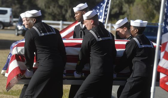 FILE - In this Dec. 16, 2019 file photo, sailors carry the casket of Cameron Walters at Oak Hill Cemetery in Richmond Hill, Ga. Walters was one of the three Navy sailors killed in a Saudi gunman's attack at Pensacola Naval Air Station in Florida on Dec. 6. The FBI has found a link between the gunman in a deadly attack at a military base last December and an al-Qaida operative. That's according to a U.S. official who spoke to The Associated Press on Monday.  (Steve Bisson/Savannah Morning News via AP)