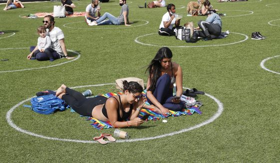 Two young women relax in a circle marked on the grass for proper social distancing in Brooklyn's Domino Park as others do the same to prevent the spread of coronavirus, Monday, May 18, 2020, in New York. The small park, which offers good views of the Manhattan skyline and the Williamsburg bridge, was the site of severe overcrowding during a spate of unseasonably warm weather just over a week ago. The circles have been added to promote good behavior on the park of park visitors. (AP Photo/Kathy Willens)