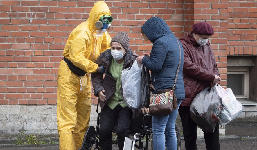 A medical worker wearing protective clothing helps a woman out of her wheelchair as she leaves after receiving treatment at a hospital for COVID-19 patients in St. Petersburg, Russia, Monday, May 18, 2020. (AP Photo/Dmitri Lovetsky)