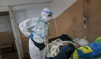 In this photo taken on Saturday, May 9, 2020, Dr. Olha Kobevko speaks to a patient suspected of having coronavirus at the regional hospital in Chernivtsi, Ukraine. The hospital lacks a centralized oxygen supply and has to rely mostly on refillable oxygen masks, reflecting a pitiful state of Ukraine's underfunded health care system that was quickly overwhelmed by the coronavirus even with a relatively low number of infections. (AP Photo/Evgeniy Maloletka)