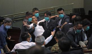 Pan-democratic legislator Lam Cheuk-ting, is taken away by security during a Legislative Council's House Committee meeting in Hong Kong, Monday, May 18, 2020. Scuffles broke out in Hong Kong's legislature for a second time this month, with security guards ejecting several pro-democracy lawmakers as the city's pro-democracy and pro-Beijing camps continue to wrestle for control over a key committee that scrutinizes bills. (AP Photo/Kin Cheung)