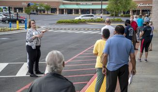 Gwinnett County elections supervisor Kristi Royston, left,  gives instructions to individuals waiting in line for early in-person voting for Georgia's primary election at the Gwinnett County Voter Registration and Elections Office in Lawrenceville, Ga., Monday, May 18, 2020. Early voting began Monday and will last three-weeks. Georgia's Election Day is Tuesday, June 9.  (Alyssa Pointer/Atlanta Journal-Constitution via AP)