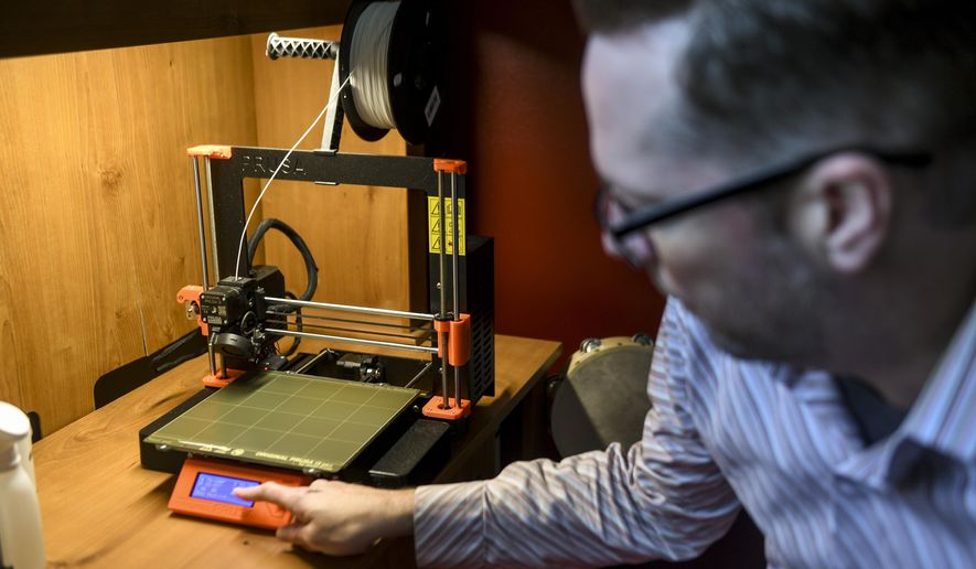 In this Tuesday, May 5, 2020 photo, Mitchell Olson resets a 3D printer to make a new batch of COVID-19 testing swabs at his home in Sioux Falls, S.D. (Abigail Dollins/The Argus Leader via AP)