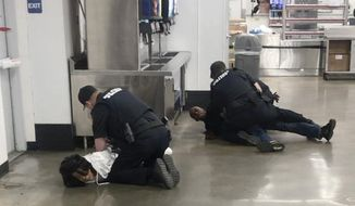 In this March 23, 2020 frame grab taken from video, Marvia Gray, left and her son Derek Gray are arrested at a Sam's Club store in Des Peres, Missouri. A lawsuit filed Monday May 18, 2020, accuses four white suburban St. Louis police officers of brutalizing Gray and her adult son after wrongly accusing them of stealing a television. Gray alleges she suffered serious and permanent injuries during her arrest. Her 43-year-old son, Derek, suffered a concussion, three shattered teeth and other injuries, according to the lawsuit.(Photo courtesy Action Injury Law Group via AP)