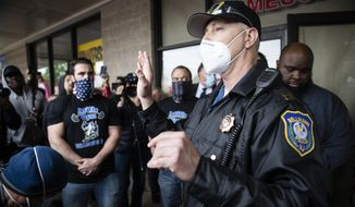 A police officer addresses supporters of Atilis Gym co-owners Frank Trumbetti, center, Ian Smith, left, outside their gym in Bellmawr, N.J., Monday, May 18, 2020. The gym in New Jersey reopened for business early Monday, defying a state order that shut down nonessential businesses to help stem the spread of the coronavirus. (AP Photo/Matt Rourke)
