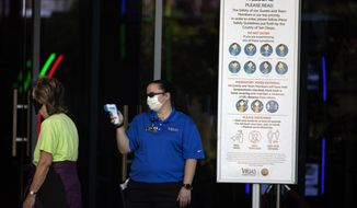 An official reads the temperature of a woman at the entrance to the Viejas Casino and Resort as it reopens Monday, May 18, 2020, in Alpine, Calif. The casino is one of several on tribal lands in Southern California set to reopen this week. (AP Photo/Gregory Bull)