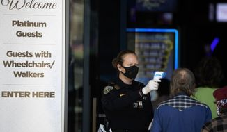 A security official checks the temperature of a man at the entrance to the Viejas Casino and Resort as it reopens Monday, May 18, 2020, in Alpine, Calif. The casino is one of several on tribal lands in Southern California set to reopen this week. (AP Photo/Gregory Bull)