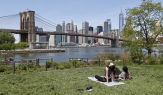 Two women, neither of whom were wearing protective face coverings, sunbathe on a grassy slope at Brooklyn Bridge Park during the current coronavirus outbreak, Sunday, May 17, 2020, in New York. (AP Photo/Kathy Willens)