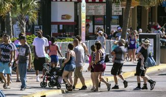 Groups cross Ocean Boulevard on Saturday, May 16, 2020, in Myrtle Beach, S.C.. With hotels, beaches, shopping and restaurants reopening along the Grand Strand, tourist season kicked off this weekend despite coronavirus concerns. (Jason Lee/The Sun News via AP)