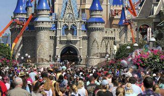 In this March 12, 2020, file photo, a crowd is shown along Main Street USA in front of Cinderella Castle in the Magic Kingdom at Walt Disney World in Lake Buena Vista, Fla. .(Joe Burbank/Orlando Sentinel via AP, FIle)