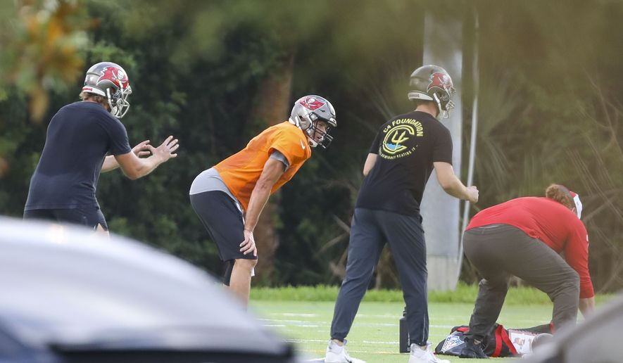Tampa Bay Buccaneers NFL football quarterback Tom Brady, center in orange, is seen working out with other players at Berkeley Preparatory School in Tampa, Fla., Tuesday, May 19, 2020. (Chris Urso/Tampa Bay Times via AP)