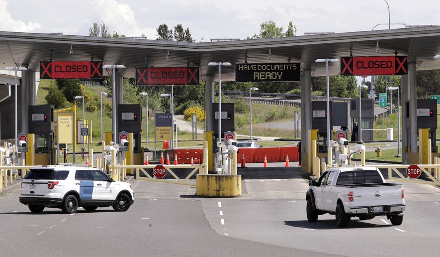 In this photo taken Sunday, May 17, 2020, a truck from Canada heads to the single open lane heading into the U.S. at the Peace Arch border crossing in Blaine, Washington. (AP Photo/Elaine Thompson) **FILE**