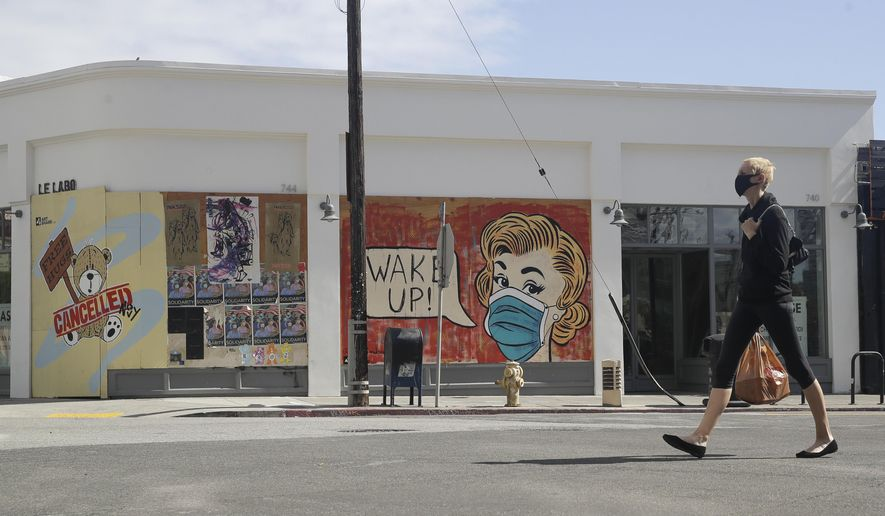 A masked pedestrian walks past a coronavirus-themed mural Monday, May 18, 2020, in the arts district of Los Angeles. (AP Photo/Marcio Jose Sanchez)