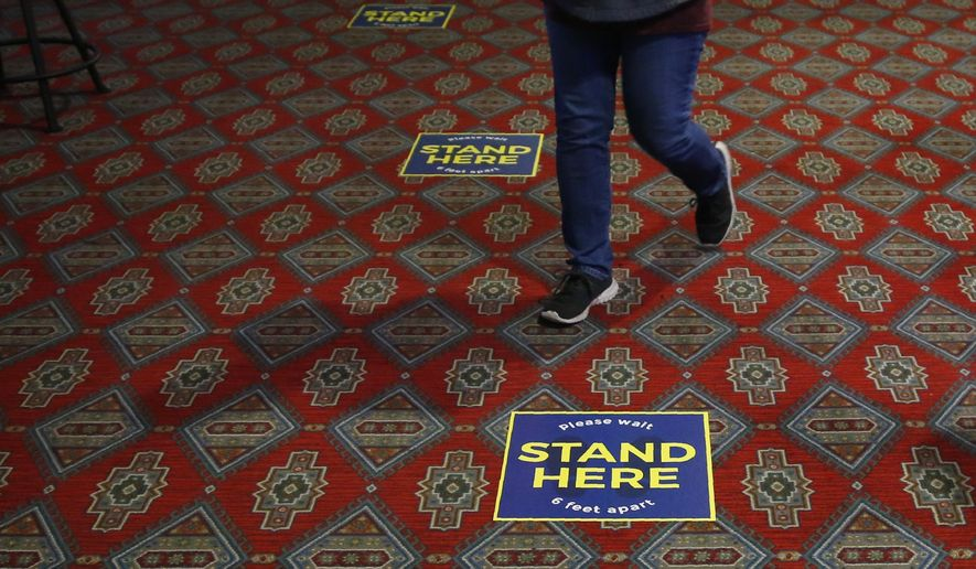 Signs to encourage social distancing are seen on the floor Tuesday, May 12, 2020, at Thunderbird Casino in Norman, Okla. The Casino, operated by the Absentee Shawnee Tribe, has reopened for business with about one-third of capacity allowed and social distancing guidelines. (AP Photo/Sue Ogrocki)