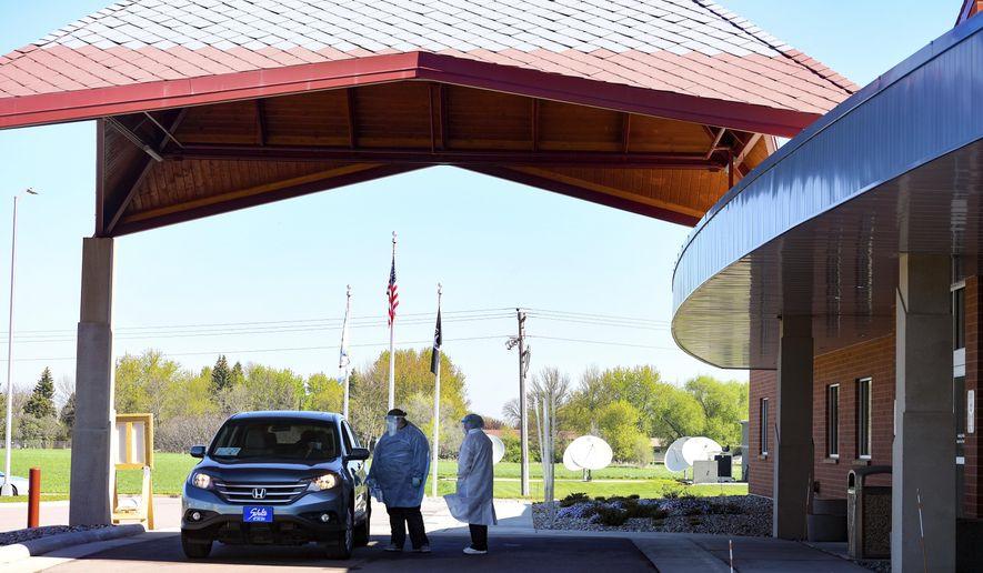 A car pulls up to the screening station on Thursday, May 14, at the Flandreau Santee Sioux Tribal Health Center in South Dakota.  (Erin Bormett/The Argus Leader via AP)