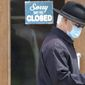 "A man walks past a closed business. A Michigan businessman is urging the public to speak up by promoting ""Take Yourself to Work Day."" (Associated Press)"