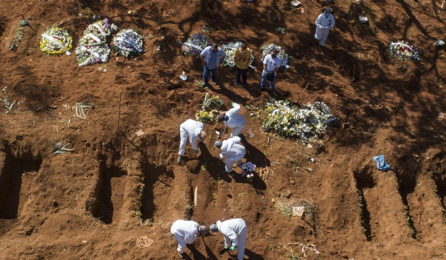 Cemetery workers in protective clothing bury a COVID-19 victim at the Vila Formosa cemetery in Sao Paulo, Brazil, Wednesday, May 20, 2020. (AP Photo/Andre Penner)