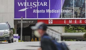 A masked man passes Wellstar Atlanta Medical Center on Boulevard in Atlanta on Wednesday, May 20, 2020 after the Wellstar Health System announced Tuesday that it would furlough more than 1,000 employees across its hospital network. The system cited a drop in patient volume due to the coronavirus pandemic as the reason for the financial measures. (John Spink/Atlanta Journal-Constitution via AP)
