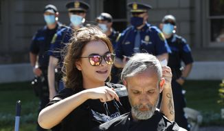 A hair stylist gives a man a free haircut at the State Capitol during a rally as the Michigan State Police watch in Lansing, Mich., Wednesday, May 20, 2020. Barbers and hair stylists are protesting the state's stay-at-home orders, a defiant demonstration that reflects how salons have become a symbol for small businesses that are eager to reopen two months after the COVID-19 pandemic began. (AP Photo/Paul Sancya)
