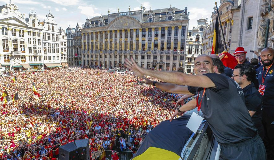 FILE - In this Sunday, July 15, 2018, photo, Belgian soccer team coach Roberto Martinez reacts on the balcony of the city hall at the Grand Place in Brussels. Martinez has signed a new contract to lead the Red Devils through the 2022 World Cup in Qatar. (Yves Herman, Pool Photo via AP, File)