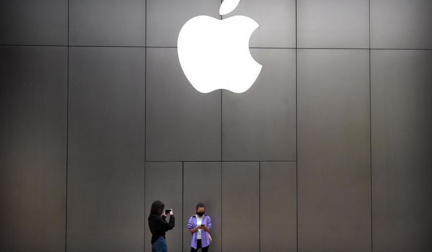 Women wear face masks to protect against the spread of the new coronavirus as they stand near an Apple store in Beijing, Friday, April 24, 2020. (AP Photo/Mark Schiefelbein) ** FILE **