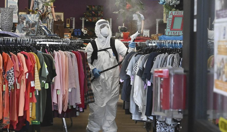 A crew equipped with electrostatic sprayers cleans a Goodwill store with a hydrogen peroxide disinfectant cleaner after several employees tested positive for COVID-19, on Tuesday, May 19, 2020, in Colorado Springs, Colo. The store is temporarily closed and no reopening date has yet been announced. But all of the other Goodwill Stores in area are reopened except the Austin Bluffs store here and the W. Colorado Ave. store. (Jerilee Bennett/The Gazette via AP)