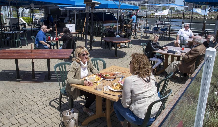 Patrons enjoy lunch on the patio of the Crab Shell restaurant, Wednesday, May 20, 2020, in Stamford, Conn. Restaurants can begin offering service in outdoor dining areas Wednesday as part of the first phase of Connecticut's statewide reopening, including in hard-hit Fairfield County on the New York state line. (AP Photo/Mary Altaffer)