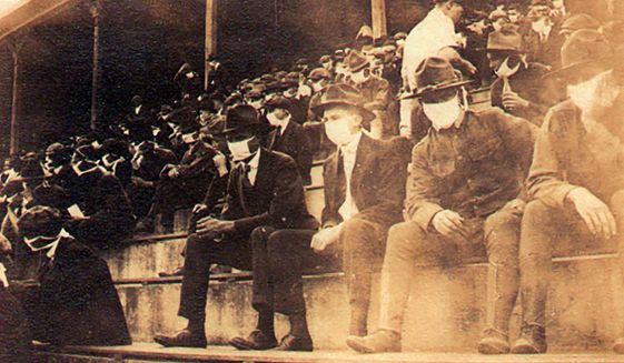 This undated photo provided by Georgia Tech alumnus Andy McNeil shows a Georgia Tech home game during the 1918 college football season. The photo was taken by Georgia Tech student Thomas Carter, who would receive a degree in Mechanical Engineering. The 102-year-old photo could provide a snapshot of sports once live games resume: Fans packed in a campus stadium in the midst of a pandemic wearing masks with a smidge of social distance between them on concrete seats. (Thomas Carter via AP)  **FILE**