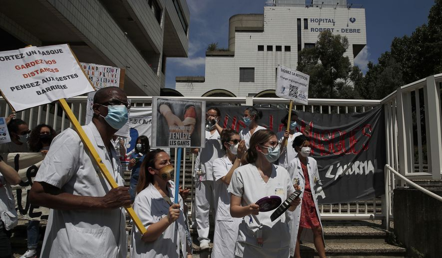 Medical staff demonstrate at the Robert Debre hospital Thursday, May 21, 2020 in Paris. French nurses and doctors demand better pay and a rethink of a once-renowned public health system that found itself quickly overwhelmed by tens of thousands of virus patients. (AP Photo/Francois Mori)
