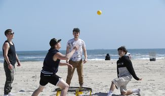 A group plays a game of spike ball at Jones Beach amid the coronavirus pandemic, Thursday, May 21, 2020, in Wantagh, N.Y. As pandemic lockdowns ease across the United States, millions of Americans are set to take tentative steps outdoors to celebrate Memorial Day, the traditional start of summer. But public health officials are concerned that if people congregate in crowds or engage in other risky behaviors, the long weekend could cause the coronavirus to come roaring back. (AP Photo/Kathy Willens)