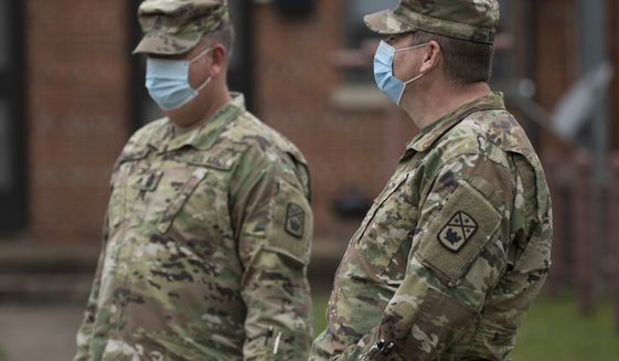 Members of the Tennessee National Guard stand outside the East Lake Courts Community Center where free COVID-19 testing was being offered to residents of East Lake Courts on Thursday, May 21, 2020, in Chattanooga, Tenn. (Troy Stolt/Chattanooga Times Free Press via AP)