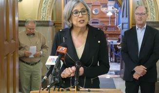 In this photo from Wednesday, May 20, 2020, Kansas Senate President Susan Wagle, R-Wichita, speaks to reporters during a news conference outside the Senate chamber in Topeka, Kan., as Senate Majority Leader Jim Denning, left, R-Overland Park, and Senate Vice President Jeff Longbine, right, R-Emporia, watch. GOP leaders hope to pass a bill curbing Democratic Gov. Laura Kelly's power to manage the coronavirus pandemic. (AP Photo/John Hanna)