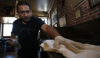 Miguel Colio cleans tables at the Goldfield Trading Post restaurant in Sacramento, Calif., Wednesday May 20, 2020. Sacramento is expecting to receive state approval for customers to dine in this week. Goldfield is expected to reopen Friday. (AP Photo/Rich Pedroncelli)