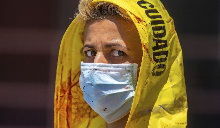 Activist Emek Echo with the animal rights network Direct Action Everywhere (DxE), wears a face mask covered with theatrical blood outside the slaughterhouse in Vernon, Calif., as workers walk out of the plant during a break on Thursday, May 21, 2020. DxE activists denounced President Donald Trump's executive order last month to keep meat processing plants open, despite the closure of numerous plants, including several owned by Smithfield, across the country due to widespread COVID-19 outbreaks and even deaths among employees. (AP Photo/Damian Dovarganes)