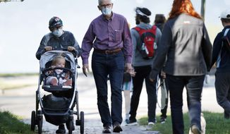 Maria and Philip Ptacin wear masks while taking a walk with their 17-month-old granddaughter, Juliette Hitchen, Wednesday, May 20, 20210, in Portland, Maine. (AP Photo/Robert F. Bukaty)