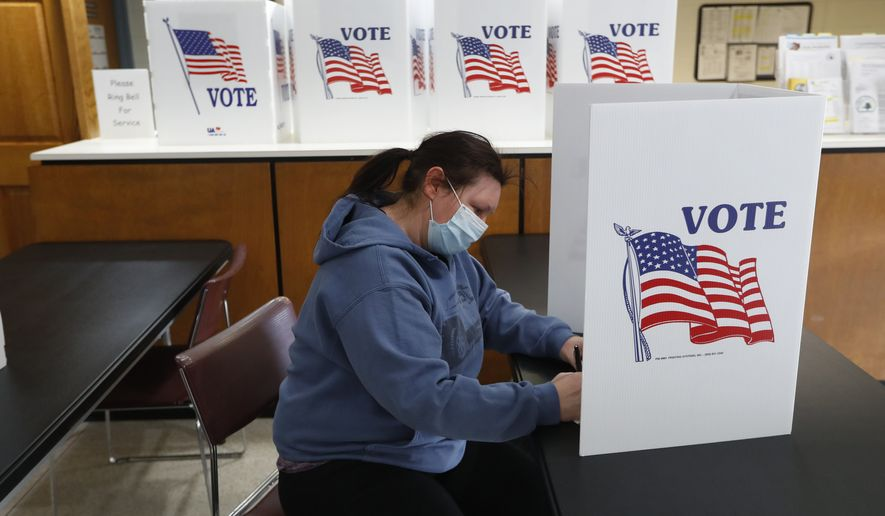 In this Tuesday, May 5, 2020 file photo, a voter fills out an absentee ballot at City Hall in Garden City, Michigan. Voting in the District of Columbia presidential primary is not open, although it will largely be conducted by mail. In-person voting stations will also be in operation in all eight wards of the city.  (AP Photo/Paul Sancya)