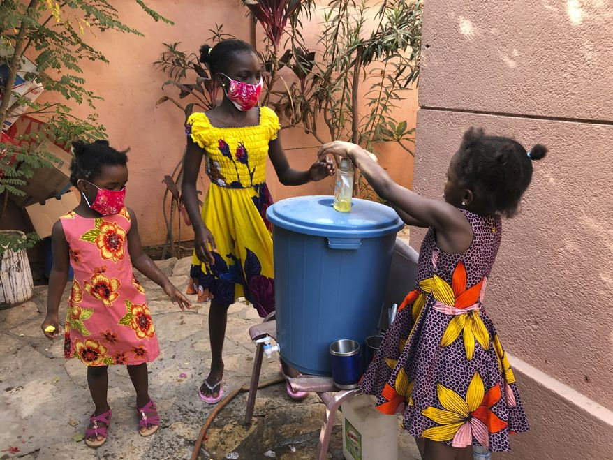 In this May 21, 2020, photo, the Larson sisters wash their hands inside the gate at their home in Dakar, Senegal. The girls were adopted from Sierra Leone after their father and other relatives died of Ebola. (AP Photo/Krista Larson)