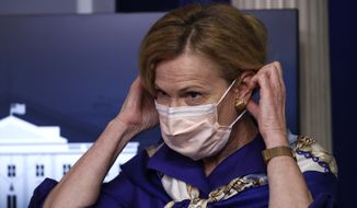 Dr. Deborah Birx, White House coronavirus response coordinator, puts on a face mask after speaking with reporters about the coronavirus in the James Brady Briefing Room of the White House, Friday, May 22, 2020, in Washington. (AP Photo/Alex Brandon)