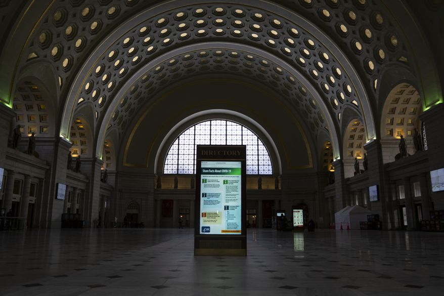 CDC information on how prevent the spread of germs and help prevent the spread of COVID-19 is illumination in the directory kiosk at a quiet Union Station in Washington, Thursday, May 22, 2020. (AP Photo/Carolyn Kaster)