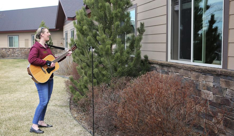 "In this April 17, 2020, photo, Kirsten Wells plays guitar for residents of Rising Mountains Assisted Living in Bigfork, Mont. She played songs like ""Take Me Out to the Ball Game,"" ""When It's Springtime in the Rockies"" and ""King of the Road."" (Mackenzie Reiss/The Daily Inter Lake via AP)"