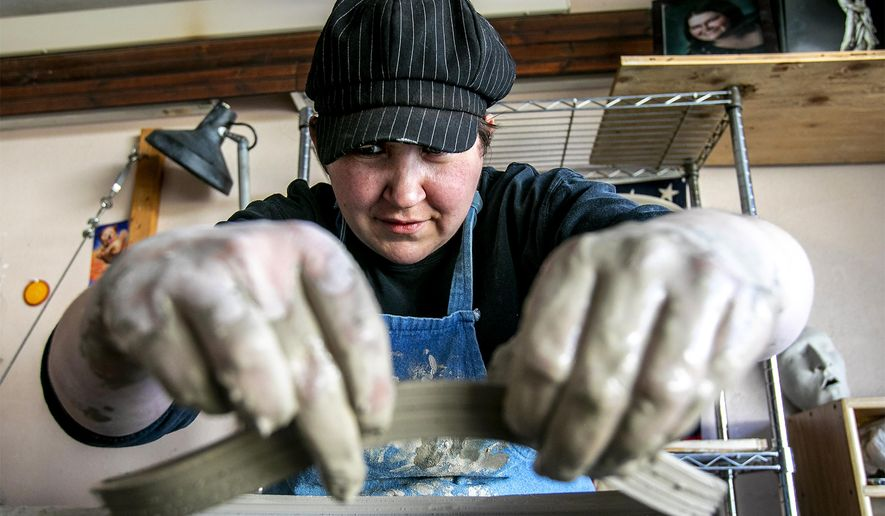 In this April 30, 2020 photo, Ariane Jimison pulls off a piece of a ceramic bowl after discovering an air pocket in the clay in her garage/pottery studio in Gillette, Wyo. One of the co-owners of Pizza Carrello in Gillette, she usually spends most of her time at the restaurant. But with the business closed during the COVID-19 pandemic, the former professional potter has been spending time behind her pottery wheel. (August Frank/Gillette News Record via AP)