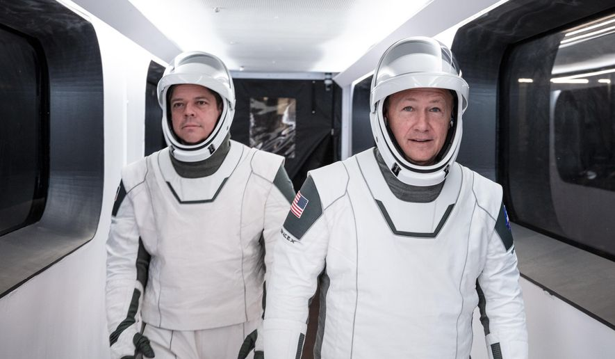 In this Jan. 17, 2020 photo made available by SpaceX, NASA astronauts Bob Behnken, left, and Doug Hurley, wearing SpaceX spacesuits, walk through the Crew Access Arm connecting the launch tower to the SpaceX Crew Dragon spacecraft during a dress rehearsal at NASA's Kennedy Space Center in Cape Canaveral, Fla. For their May 27, 2020 mission, Hurley will be in charge of launch and landing and Behnken will oversee rendezvous and docking at the International Space Station. (SpaceX via AP)