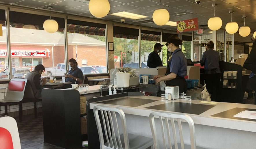 Customers sit inside a Waffle House Restaurant, Friday, May 22, 2020 in Atlanta. Vice President Mike Pence and Brian Kemp were scheduled to talk about reopening during the pandemic with members of the restaurant industry meeting at the headquarters of the popular Southern eatery, Waffle House. (Sudhin Thanawala)