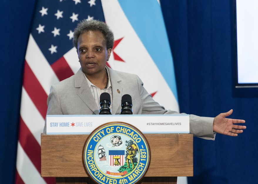 In this April 20, 2020, file photo, Chicago Mayor Lori Lightfoot speaks during a news conference in Chicago. Chicago officials say the nation's third-largest city cannot begin to loosen restrictions designed to limit the spread of the coronavirus before early June. Gov. J.B. Pritzker has said all parts of the state are on track for restrictions to begin loosening on May 29. But Mayor Lightfoot said Friday, May 22, that the city is not yet hitting the metrics in her plan for gradually loosening restrictions and that she is hopeful that can happen by early June. (Tyler LaRiviere/Chicago Sun-Times via AP, File)