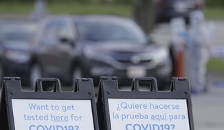Signs are posted at a drive-thru COVID-19 testing site, Friday, May 22, 2020, in Indianapolis. The state's business and gathering restrictions are being eased for most of the state beginning Friday. (AP Photo/Darron Cummings)