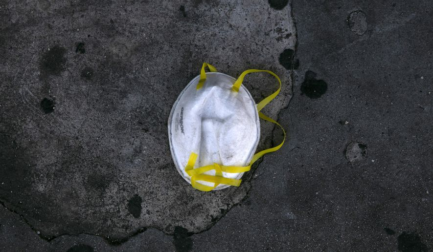 A face mask is discarded on a sidewalk during the coronavirus outbreak in the Westlake neighborhood of Los Angeles, Thursday, May 21, 2020. While most of California took another step forward to partly reopen in time for Memorial Day weekend, Los Angeles County didn't join the party because the number of coronavirus cases has grown at a pace that leaves it unable to meet even the new, relaxed state standards for allowing additional businesses and recreational activities. (AP Photo/Jae C. Hong)