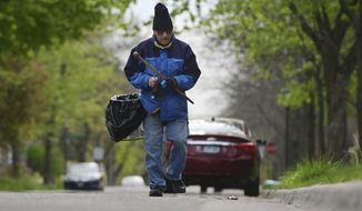Retired postal carrier Steve Dalbec scans for trash as he walks a route picking up trash along the sidewalks and streets in his St. Paul neighborhood on Wednesday, May 13, 2020. Dalbec spends a couple of hours on four days each week patrolling his Midway neighborhood streets and sidewalks for trash, using his homemade trash stick and filling a basket strapped to his hip. (John Autey/Pioneer Press via AP)